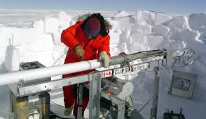 A scientist removing a freshly drilled core from an antarctic field site (NSIDC)